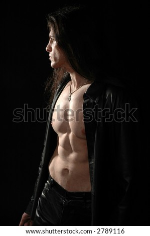 A muscular man caught in a shaft of light at night - stock photo