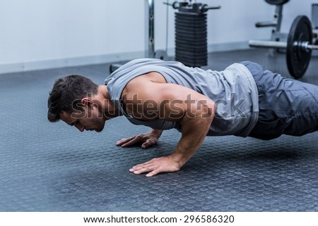 A muscular man doing a pushups at the crossfit gym - stock photo