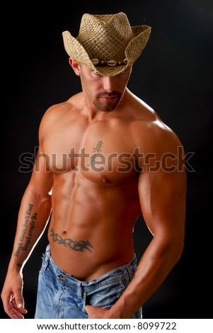 A muscular man in a cowboy hat - stock photo