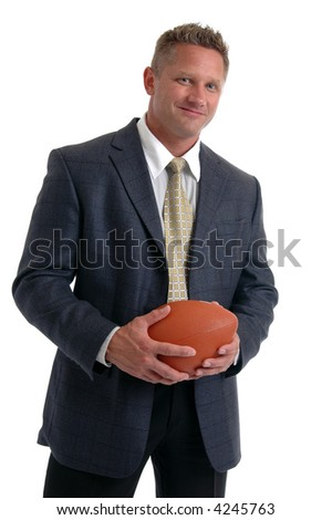 A muscular man in a suit holding a football - stock photo