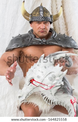 A muscular man in costume viking with dragon head