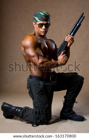 A muscular man with a gun. The guy in the soldiers' boots standing on one knee - stock photo