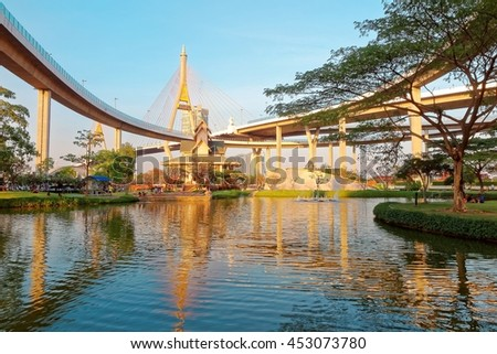 A museum by the lake in Lat Pho Park under Bhumibol Bridge Bridge (or Industrial Ring Road) in Bangkok, Thailand ~ Scenery of elevated highway interchanges and bridge towers reflecting on lake water - stock photo