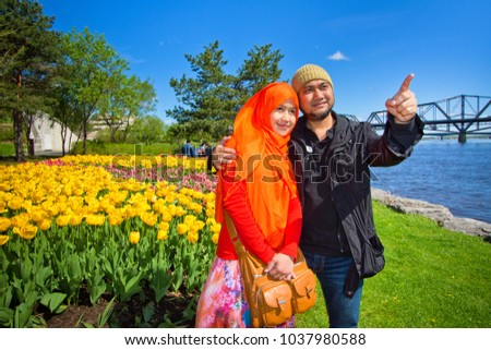 A Muslim couple from Asia taking picture with tulip flowers as background during Ottawa tulip festival