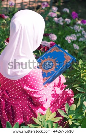 A Muslim girl reads the Quran at the blossomed garden. - stock photo