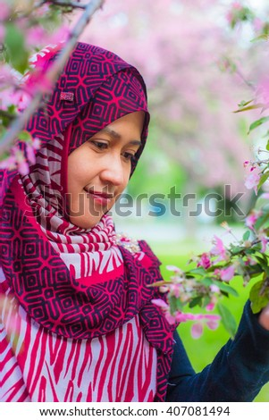 A muslim women with sakura trees as background - stock photo