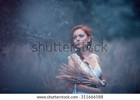 A mysterious woman in the summer garden in the evening, a mysterious female image - stock photo