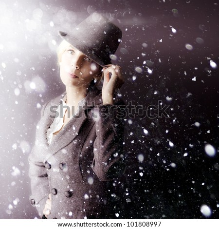 A mysterious woman operative in a hat and coat stands waiting out in a snowstorm as she watches and spies on her assigned target