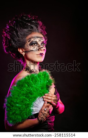 A mysterious young girl in masquerade mask holds in her hands a fan. Girl flirts.