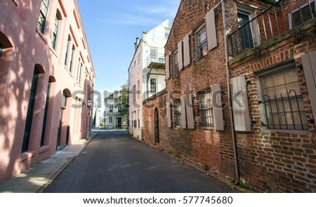 A narrow alley street runs through historic colorful houses in Charleston, South Carolina.