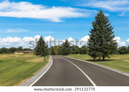 A narrow asphalt road with markings in a park - stock photo