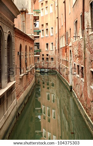A Narrow Canal Reflecting the Buildings in Venice, Italy
