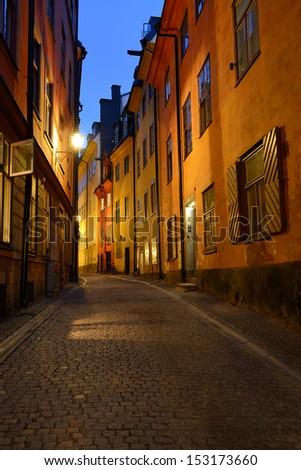 A narrow empty street at night, Gamla Stan, Stockholm, Sweden - stock photo