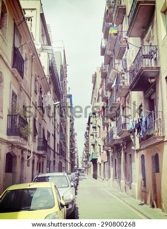 A narrow street in Barcelona with cars parked in the side. Image has a vintage effect.