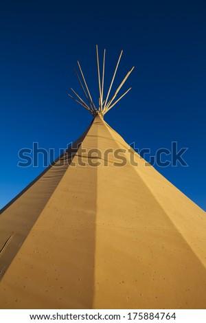 A native american tee-pee tent in orange sunset - stock photo