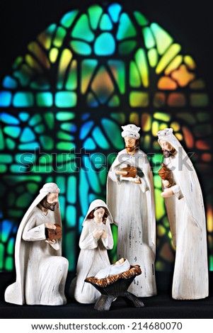 A nativity scene composed of the 3 magi, Mary and the baby Jesus set before a stained glass window. - stock photo