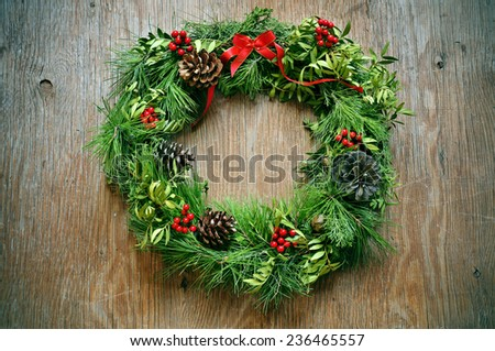 a natural christmas wreath with pine cones, berries and a red ribbon bow hanging on a rustic door