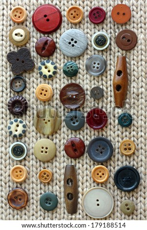 a natural colored collection a various vintage wood sewing buttons are in rows on a background of soft woven tan fabric. - stock photo