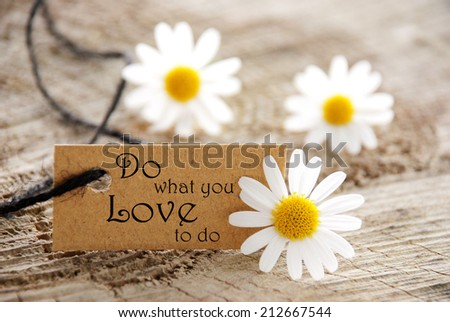 A Natural Looking Label with the Life Quote Do What You Love To Do and white Flowers - stock photo