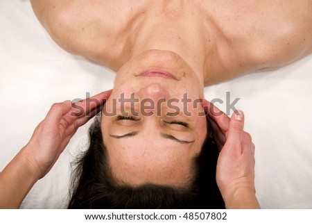 a natural mature woman having a massage at jaw and at her masseters - stock photo