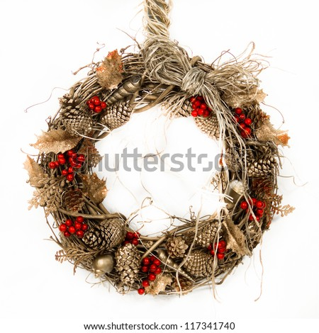 A natural twig wreath is decorated with pine cones, red berries, gold shells and a raffia bow. - stock photo