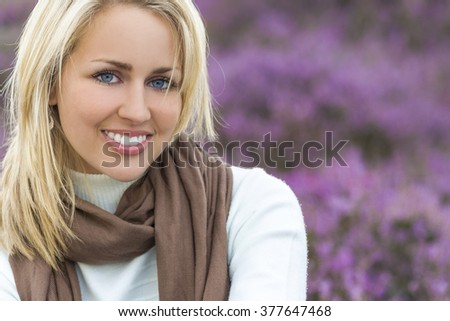 A naturally beautiful young blond woman shot in a field of out of focus heather - stock photo