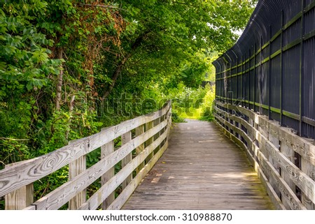 A nature trail with a wooden bridge in Mercer County NJ. - stock photo