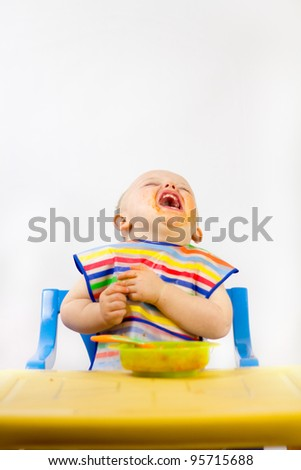 A naughty infant eating messily with his food all over his face. Shot against white copy space.