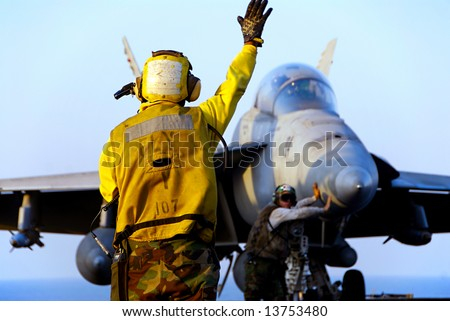 A Navy Sailor directs an F-18 Hornet fighter aircraft around the flight deck of an aircraft carrier