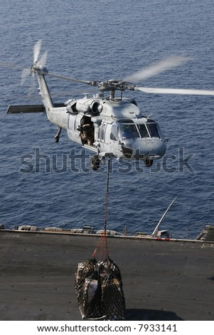 A Navy SH-60 Helicopter Performs Replenishment At Sea On the Nuclear Aircraft Carrier, USS Enterprise - stock photo