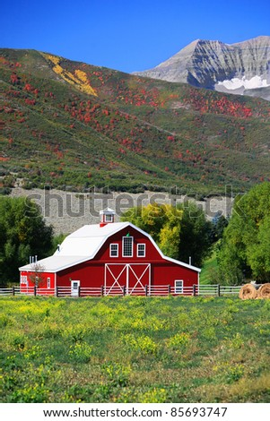 A neat, clean red barn in a green field, with rolls of hay and hills in the background where the leaves are turning fall colors, and higher mountains behind. - stock photo