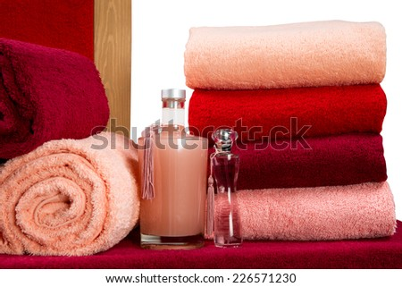 a neat stack of terry towels on a rack isolated on white background - stock photo