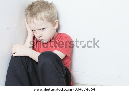 A Neglected lonely child leaning at the wall - stock photo