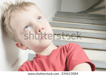 A Neglected lonely child leaning at the wall arm cross - stock photo