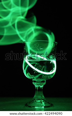 A neon glowing party drink illuminated in the nightclub.