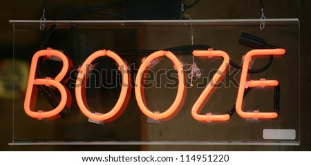 A neon sign in a window that reads Booze - stock photo