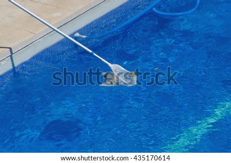 A net removing leaves of the swimming pool. Pool cleaning in summertime - stock photo