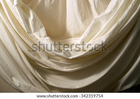 A neutral off white muslin backdrop is draped with theatrical folds filling entire image. - stock photo