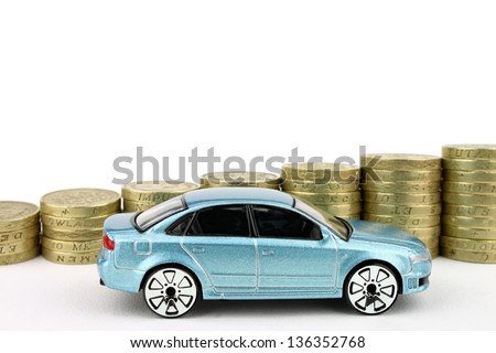 A new car next to a rising stack of coins, above which is an isolated white background. - stock photo