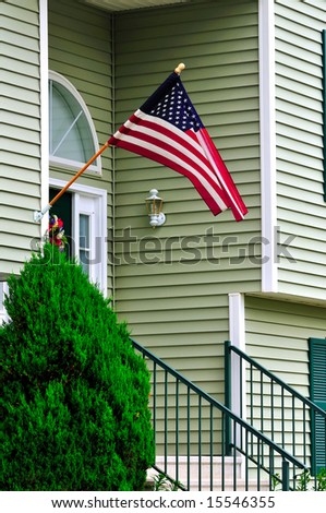 A new colonial house with American flag at the door - stock photo