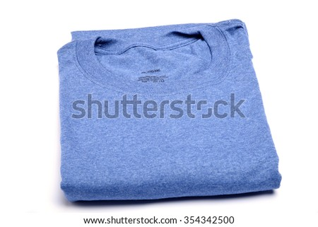 A new folded blue t-shirt on a white table from a high angle view - stock photo