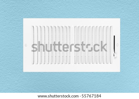 A new heating and air conditioning wall vent on a blue textured wall. - stock photo