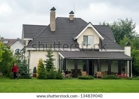 A new house with a garden in a rural area under beautiful sky in spring - stock photo