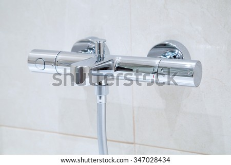 A new modern Thermostatic shower faucet on the wall in bathroom