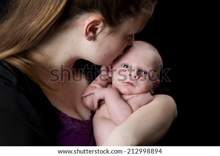 A new mother kissing her infant son.  Isolated on black. - stock photo