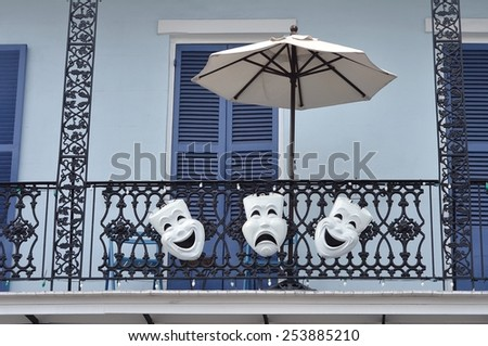 A New Orleans French Quarter balcony with umbrella, blue shutters, black wrought iron railing and Mardi Gras masks decorations. - stock photo