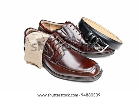 A new pair of brown leather dress shoes with argyle socks and a black belt