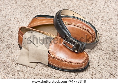 A new pair of tan leather shoes with socks and belt on beige carpet - stock photo