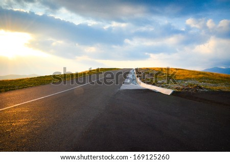 A new road over the mountains with a beautiful sunset sky and clouds view - stock photo