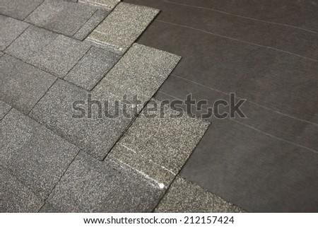 A new roof during shingle application - stock photo